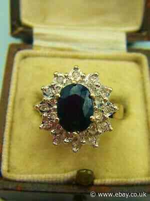A Dark Sapphire With A Diamond Gallery, Set In Hallmarked 9ct Gold.