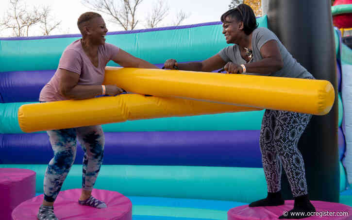 Adults bounce their way to fun at traveling inflatable playground