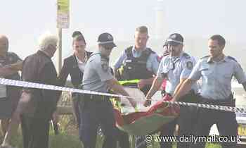 Body is removed from a beach south of Sydney as early morning surfers watch on in horror