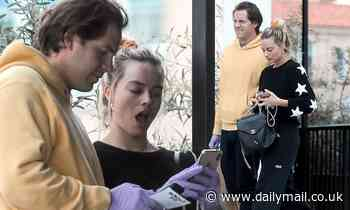 Margot Robbie and husband Tom Ackerley wear latex gloves as they wait in line at the grocery store