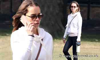 Emilia Clarke keeps things casual in a white hoodie and leggings as she walks her pooch Ted - Daily Mail