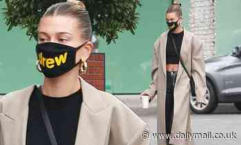 Hailey Bieber flashes her bare midriff as she picks up her morning cup of coffee