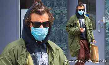 Harry Styles covers up in a protective face mask as he goes shopping in north London