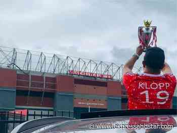 Liverpool fan takes replica Premier League trophy for photo at Old Trafford - expressandstar.com