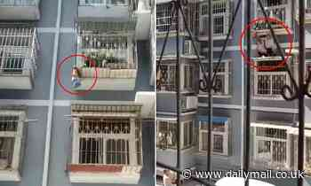 Neighbours save toddler dangling from a three-storey window