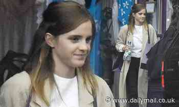 Emma Watson cuts a stylish figure in a stone trench coat while lingerie shopping