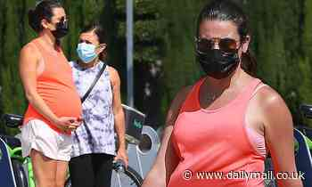 Lea Michele cradles her tank-top clad baby bump as the actress takes a stroll with mom Edith