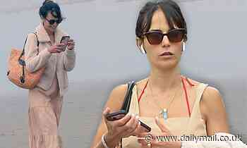 Jordana Brewster bundles up in fleece coat and nude dress on beach outing