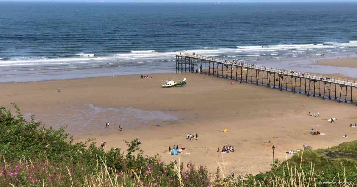 Unconscious woman pulled from sea at busy beach and airlifted to hospital