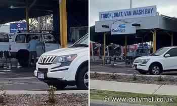 Car wash worker sprays INSIDE of car with high-pressure hose