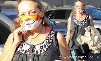 Carole Baskin shows off her wild side in a tiger mask as she arrives to the DWTS studio