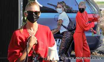 Stella Maxwell cuts a striking figure in a red tracksuit before larking around with a pal in LA