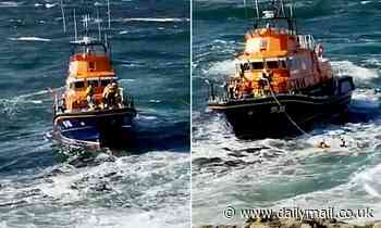 Lifeboat rescuer leaps into raging waves to save teenager from being pulled out to sea by the tide