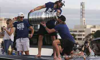 Lightning players and fans ignore COVID-19 guidelines by chugging beer from the Stanley Cup
