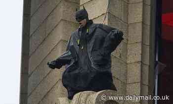 Batman stunt double is strapped to a harness as he leans over Royal Liver Building in Liverpool