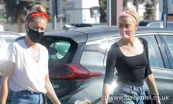 Amber Heard looks in good spirits as she joins lookalike sister Whitney and her nephew