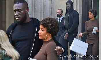 Stormzy cuts a casual figure in a black hoodie as he visits an art exhibition with his assistant