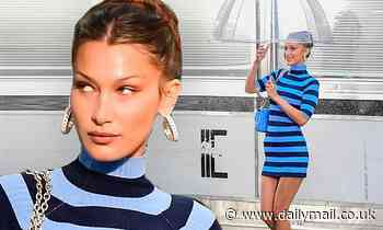 Bella Hadid parades her toned legs in a blue and black striped dress for a Michael Kors photo shoot