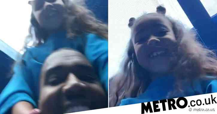 Kanye West beams with joy as he sings with North West on his shoulders