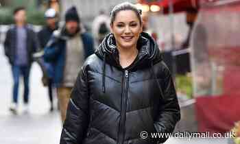 Kelly Brook wears black padded jacket and jeans at Heart FM studios