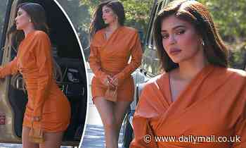 Kylie Jenner accentuates her bombshell curves in orange leather mini dress