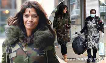 Jenny Powell wraps up in a camouflage coat as she donates a bag of clothes to a struggling mother