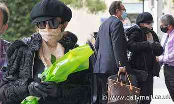 Joan Collins, 87, and husband Percy Gibson, 55, are greeted by fans outside their Madrid hotel