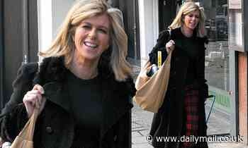Kate Garraway cuts a stylish figure in a long black coat and red tartan trousers