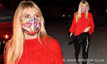Heidi Klum looks chic in black vinyl trousers and a red knit