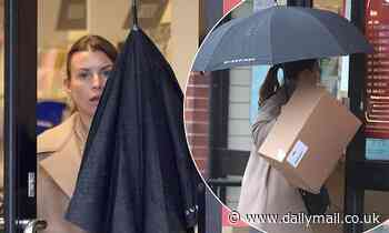 Coleen Rooney shields herself from downpour as she heads to the post office