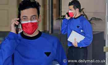Rami Malek color blocks in blue sweatshirt and red face mask heading to his car in West Hollywood