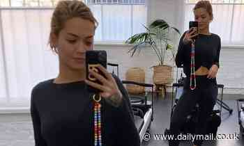 Rita Ora shows off a glimpse of her abs in a black top and gym leggings