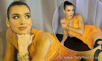 Dua Lipa smoulders in a plunging orange fishnet mini dress with racy leather thigh-high boots