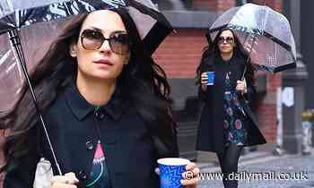 Famke Janssen doesn't let the rain stop her from putting on a leggy display in NYC