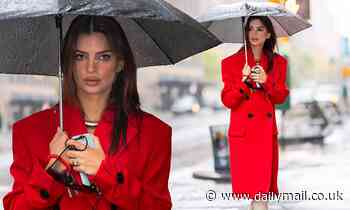 Emily Ratajkowski covers her growing baby bump in a red trench coat in rainy New York City