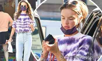 Alessandra Ambrosio stops for gas in LA wearing eye-catching purple tie dye top and pale blue jeans