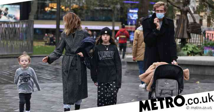 Abbey Clancy and Peter Crouch mask up for cute family stroll around fountains in Leicester Square