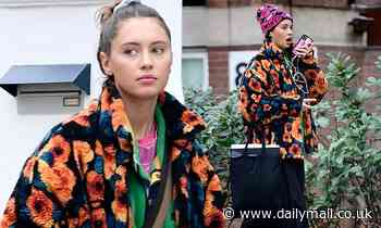 Iris Law wears quirky floral fleece with beanie hat