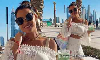 Jess Wright flashes her taut waist in a lacy white crop-top and matching mini-skirt in Dubai