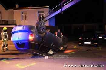 Bestuurder over de kop na botsing op geparkeerde auto