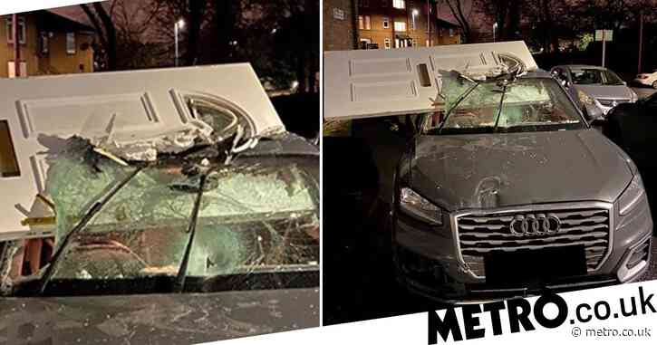 Car drives off with front door lodged in windscreen after crashing into house