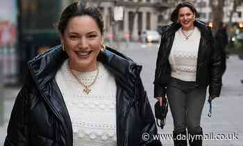 Kelly Brook cuts a casual figure in a white jumper and grey skinny jeans on her way to work