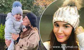 Smiling Coleen Rooney cuddles up to son Cass for a cosy garden snap