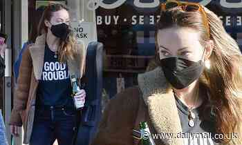 Olivia Wilde rocks a casual brown fleece jacket as she picks up a guitar in LA on Black Friday