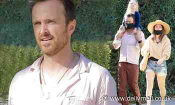 Aaron Paul sits daughter Story, two, on his shoulders as he and wife Lauren step out for a stroll