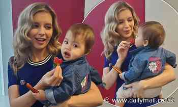 Rachel Riley feeds her baby daughter Maven strawberries at work in sweet snaps