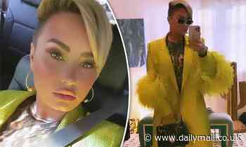 Demi Lovato looks fierce in a feathered yellow coat as she shows off her edgy blonde pixie cut