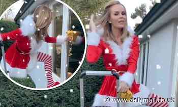 Amanda Holden continues to channel sexy Santa as she cleans her windows