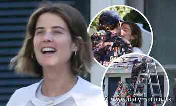 Cobie Smulders and Taran Killam share a kiss as they decorate their home with Christmas lights
