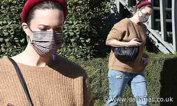 Mandy Moore looks cozy as she covers up her growing baby bump in a brown sweater while stepping out